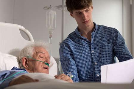 enfermos: Foto del hijo leyendo sus resultados m�dicos padre enfermo Foto de archivo