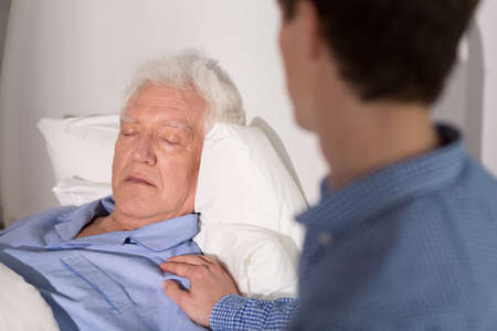 chory: Widok starszego mężczyzny z zasypianiem i jego względnej Zdjęcie Seryjne