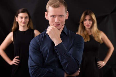 narcissistic: Handsome macho and seductive women in background Stock Photo