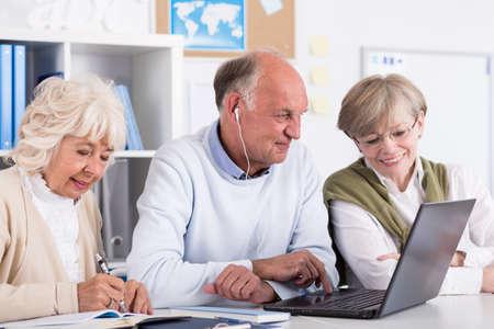 Foto van ouderejaars studenten met behulp van de computer als leermiddel