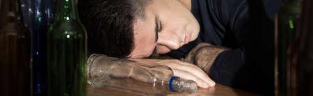 overuse: Unconscious drunken man sleeping on the table