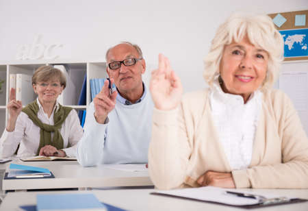 raising: Photo of retired people raising their hands during lesson