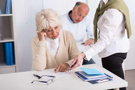 third age: Image of teacher helping worried aged female during exam Stock Photo