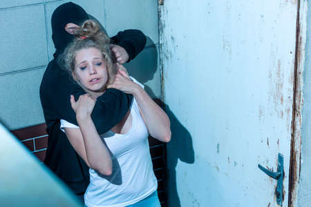 defenceless: Young woman is trying to break free from kidnapper Stock Photo