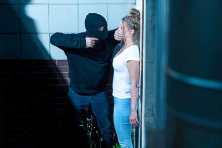 defenceless: Gunman is hushing young and scared woman Stock Photo