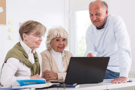 Image of elderly students sitting beside laptop in classroom