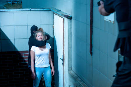 gunman: Gunman is holding scared and defenceless woman Stock Photo
