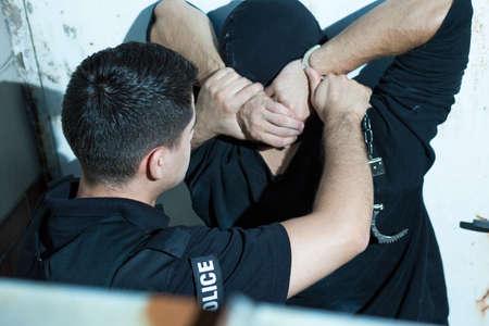 용감한 경찰관이 범죄자에게 수갑을 댔다. 스톡 콘텐츠