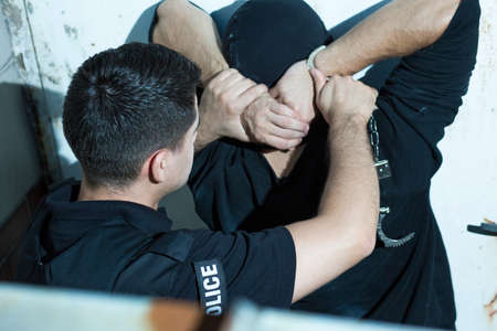 Brave police officer is putting handcuffs on a criminal Stock Photo
