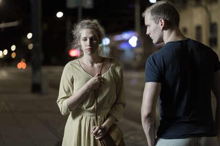 젊은 남자가 무서워하고 외로운 여자를 괴롭 히고있다. 스톡 콘텐츠