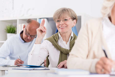 happy seniors: Photo of happy senior female raising hand during exam