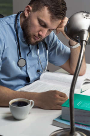 night shift: Image of sleepy doctor with coffee working at office
