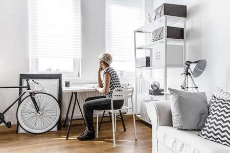 reflexionando: Mujer de pensamiento que se sienta en el escritorio en estudio moderno