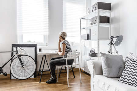 minimalist apartment: Thinking woman sitting at the desk in modern studio Stock Photo