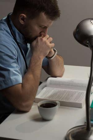 hardworking: Photo of hardworking handsome surgeon sitting at desk