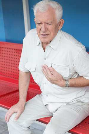 chest pain: Man having heart attack on the bus stop