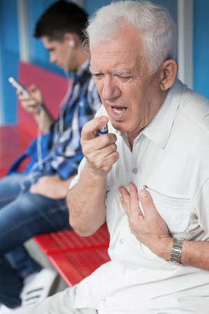 dolor de pecho: Hombre mayor con la toma de dolor en el pecho nitroglicerina Foto de archivo