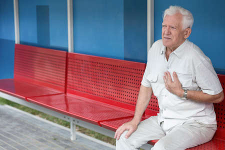 chest pain: Senior man having pain in chest outdoors Stock Photo