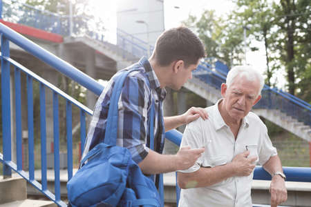 Helpful young man talking with male retiree
