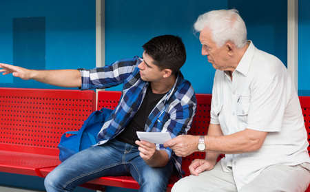 help people: Horizontal view of young man helping retiree Stock Photo