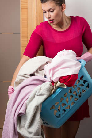 pedant: Housewife carrying too heavy load of laundry Stock Photo