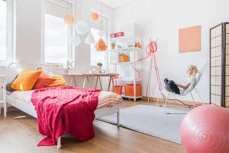 modern bedroom: Blonde teen girl relaxing in her bedroom Stock Photo