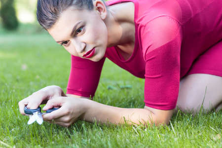 Perfect housewife is cutting grass with scissors Stock Photo