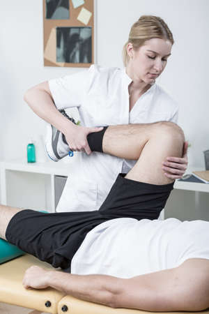 physical therapist: Image of young female physiotherapist working with male patient