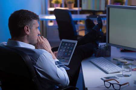 company employee: Man during night shift in office thinking about new idea