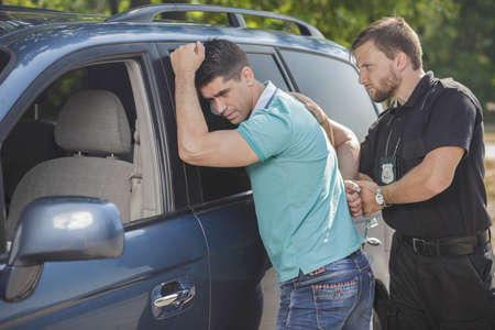 Police officer arresting young male drunk driver