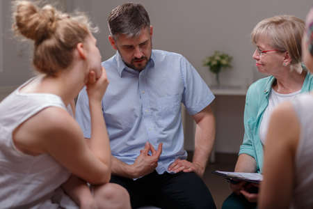 terapia psicologica: Hombre de negocios hablando de sus problemas durante la sesión de terapia de grupo