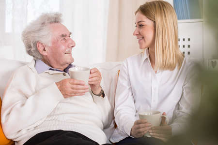 care at home: Photo of volunteer in care home talking with old man Stock Photo