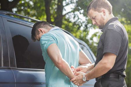 Middle aged cop putting handcuffs on drunk driver Stock Photo