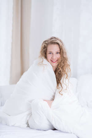 white woman: Girl in bed covered by white duvet