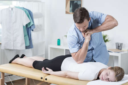 lying on back: Image of handsome male physiotherapist massaging womans back Stock Photo