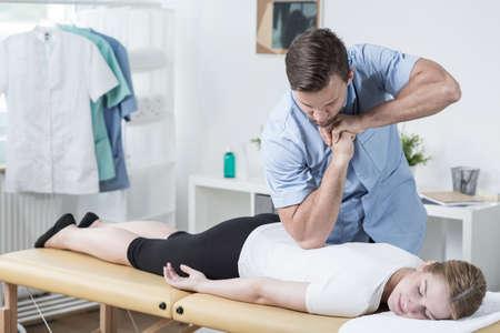 dolor espalda: Imagen de la mujer fisioterapeuta masajear la espalda masculino hermoso Foto de archivo