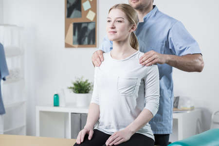 physical therapist: Image of physical therapist helping female patient with back pain