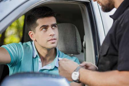 警官と話しているハンサムな若いドライバー