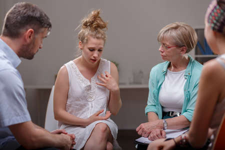 session: Young woman participating in group therapy session