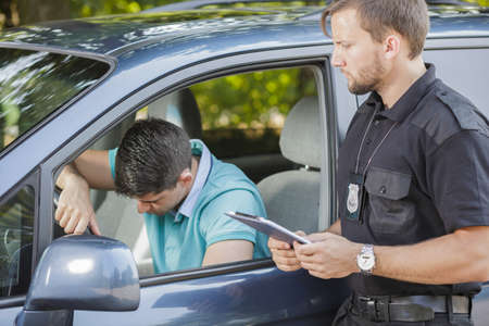 police: Broken down young driver stopped by police officer Stock Photo