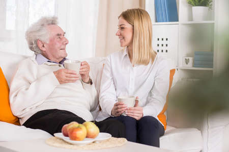 home nursing: Photo of elderly man and young volunteer in nurisng home Stock Photo