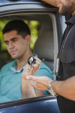 drunk: Police officer taking the car keys from young drunk man Stock Photo