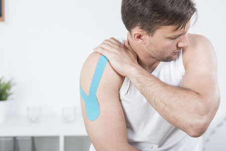 arm pain: Picture of athletic man with arm pain during kinesiotherapy