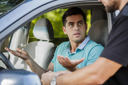 Confused young man in the car stopped by policeman Stock Photo