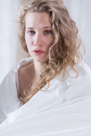 duvet: Sad crying woman covered by white duvet Stock Photo