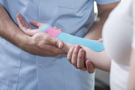 fisioterapia: Cierre de la mujer con dolor en la mano durante la terapia kinesiotaping