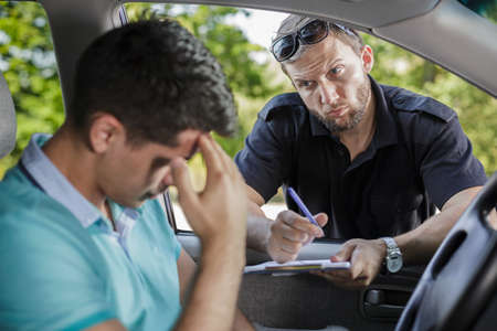 traffic control: Man in a car and the policeman with traffic ticket