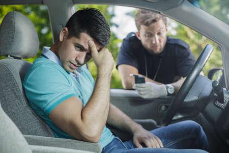 Conductor joven preocupante atrapado en la conducción después del alcohol