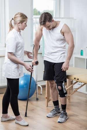 fisioterapia: Imagen del hombre con ortesis de rodilla en la sala de fisioterapia