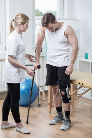 knee: Picture of man with knee orthosis in physiotherapy room